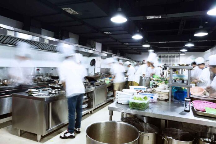 Modern professional kitchen with many workers moving around (blurred).