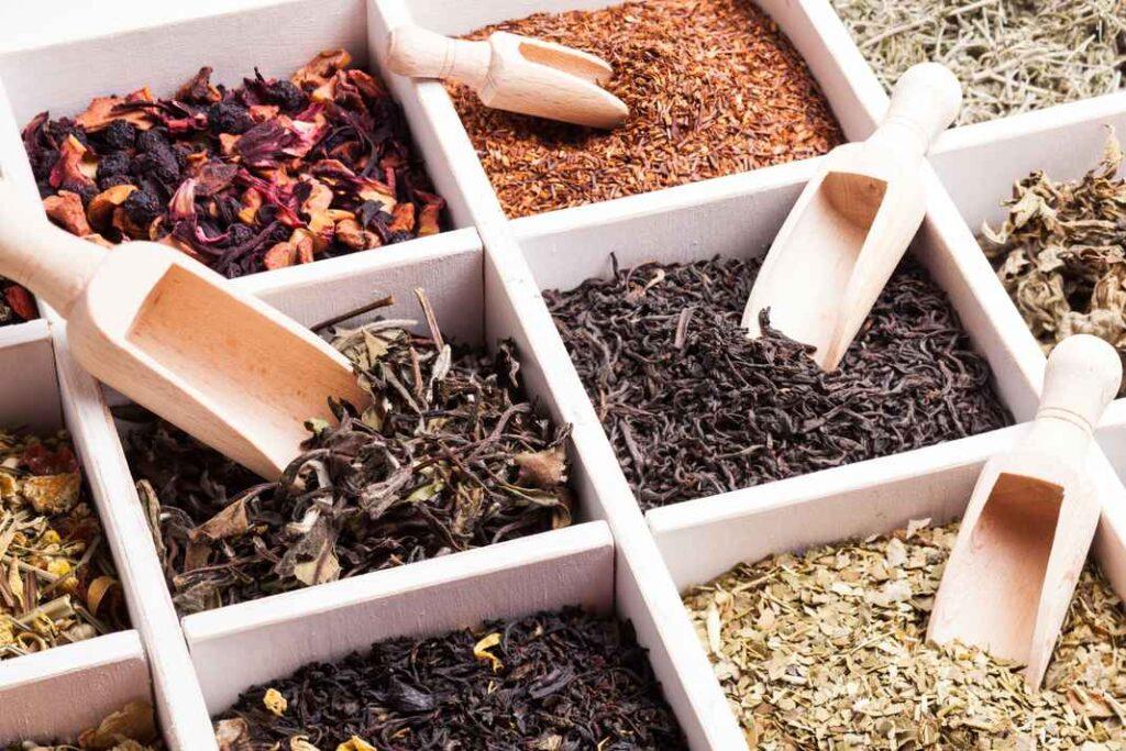 Six varieties of loose leaf tea in shades of brown, black, and green.