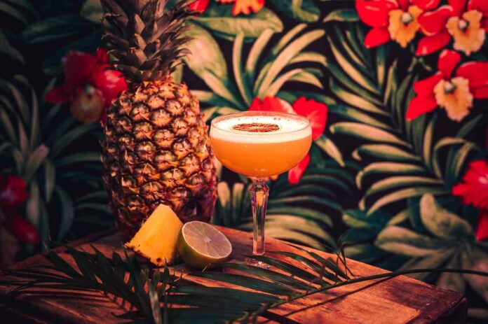 Cocktail in a stemmed glass garnished with an orange slice against tropical print backdrop with pineapple and lime.
