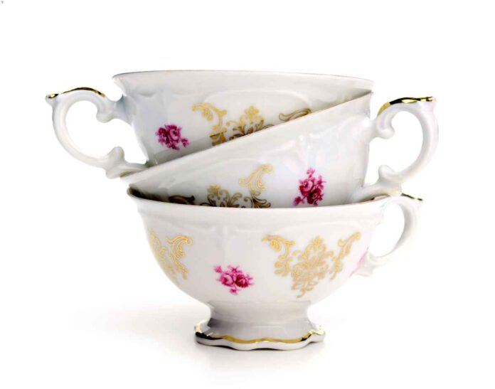 Three white, pink, and gold teacups stacked within each other.