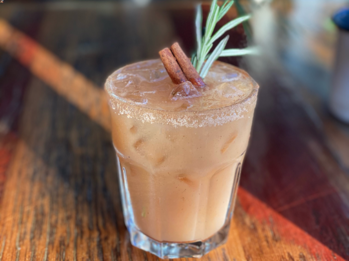 Tan cocktail in a glass garnished with cinnamon stick and rosemary sprig.