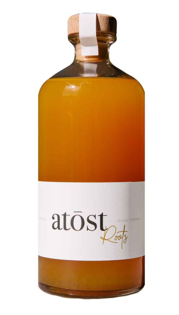 Glass bottle filled with orange liquid and labeled with Atōst Roots.