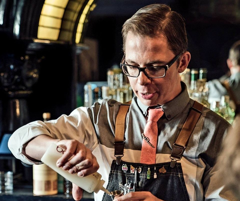 White man wearing glasses, apron, and a tie mixing a cocktail.