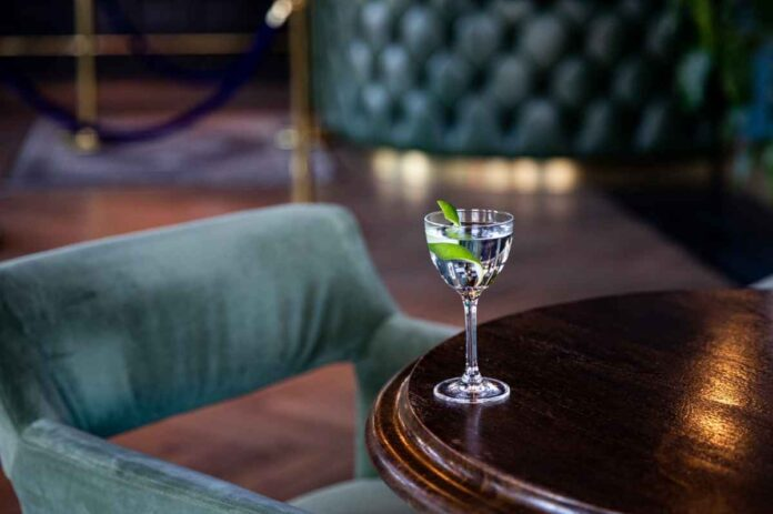 Stemmed glass filled with clear nonalcoholic cocktail and garnished with lime peel, sitting on a dark wood table next to upholstered chair.