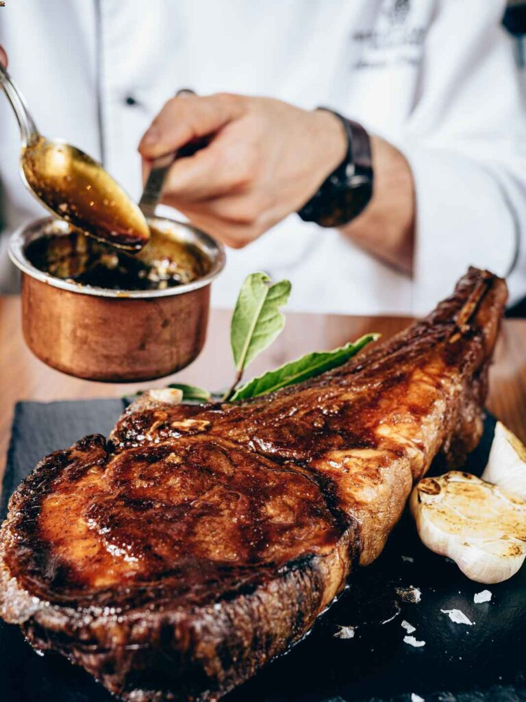 Photo of large t-bone steak with dark glaze being spooned over it.