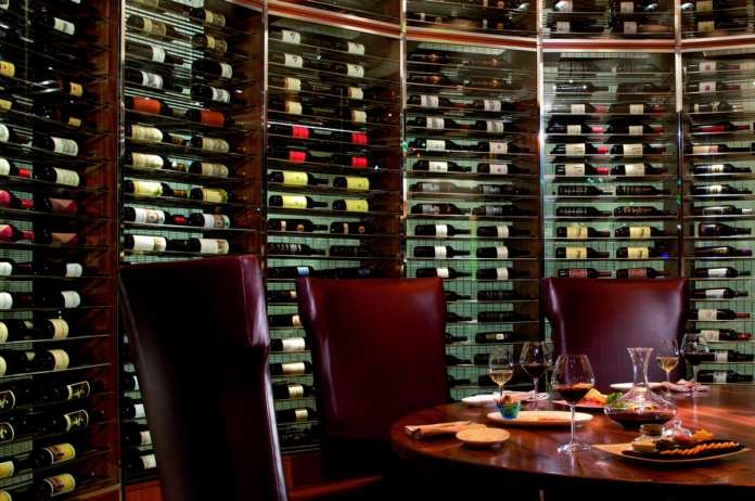 Round wooden dinner table in wine cellar with built-in wine racks lining all walls filled with bottles of wine.