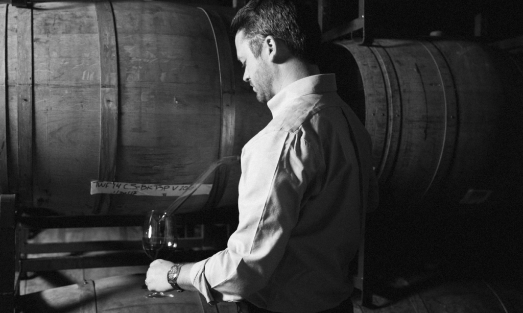Black and white photo of white man pouring wine into a wine glass directly from a barrel.