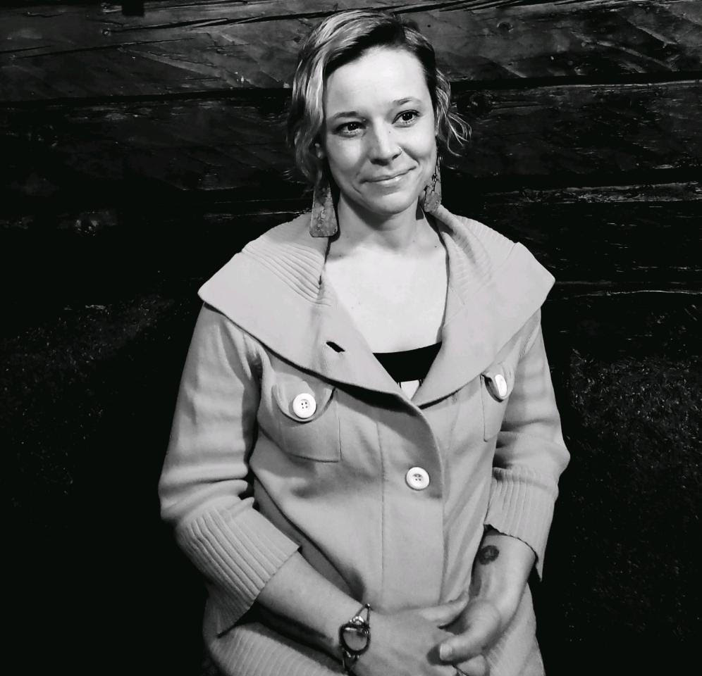 Black and white photo of smiling white woman with blonde hair wearing a sweater.