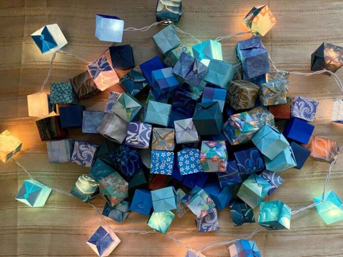 Pile of folded paper boxes in various shades of blue with string lights inside.