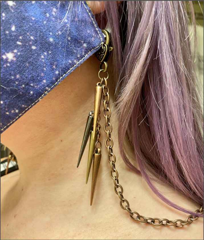 Close up of woman wearing a face mask held on by a gold chain with dangling metal embellishments.