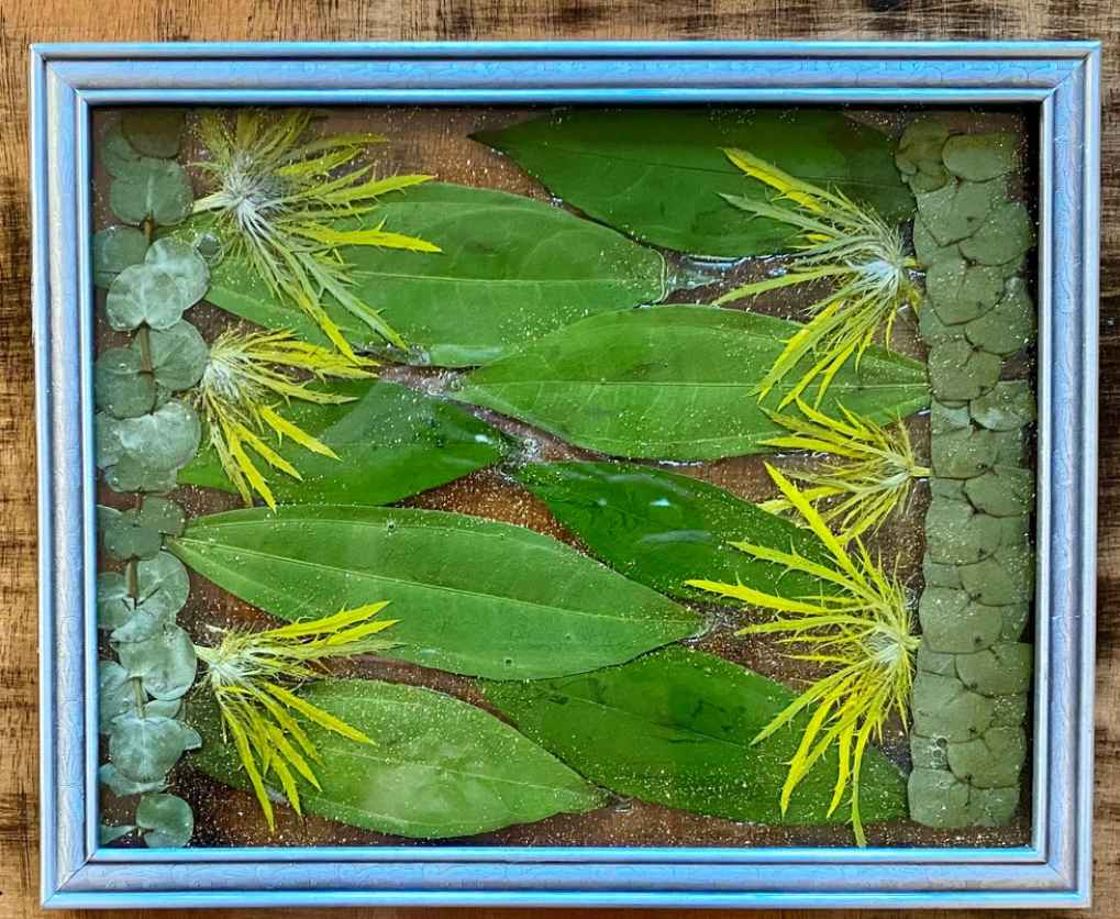 Arrangement of green and yellow leaves and blossoms laid flat in a blue picture frame.