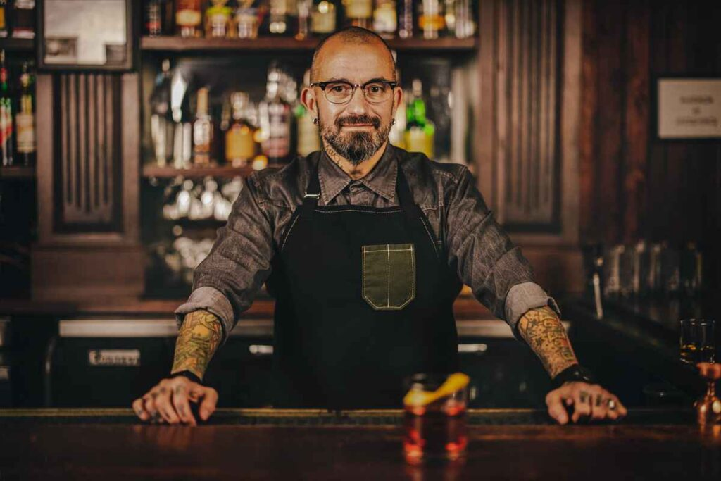 Smiling white man with tattoos, beard and glasses wearing an apron and standing behind a wooden bar.