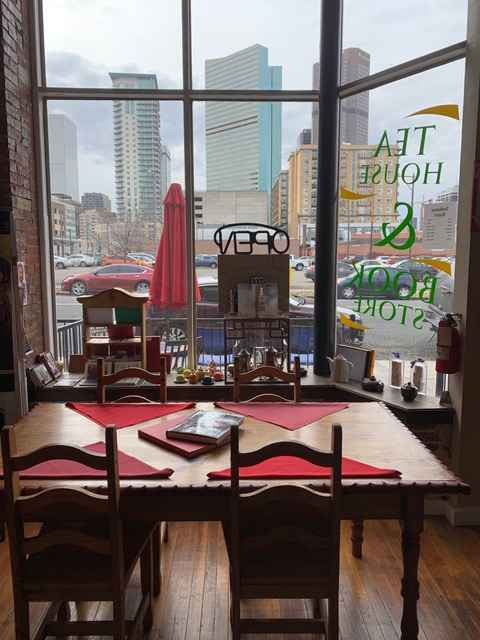 Restaurant table for four in front of storefront window that looks out over Denver's skyline.