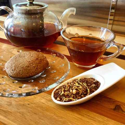 Glass teapot and teacup on wooden table next to a spoonful of loose tea leaves and a whole wheat roll.