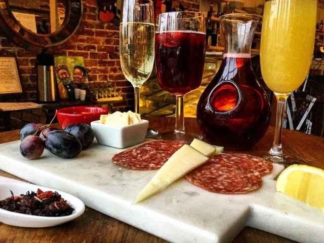 Glasses of red and white wine next to charcuterie board.