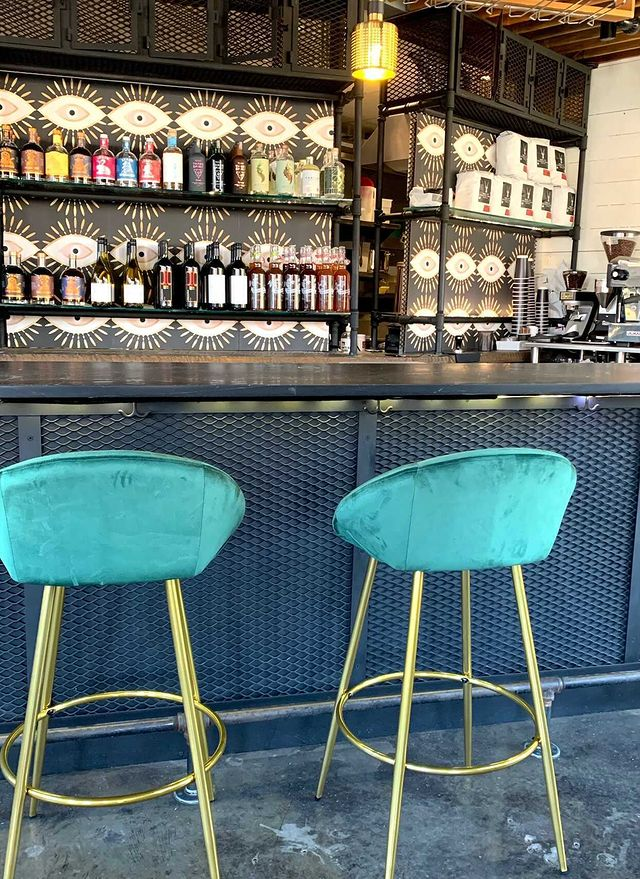 Teal velour bar stools in front of bar stocked with nonalcoholic beverages of all types.