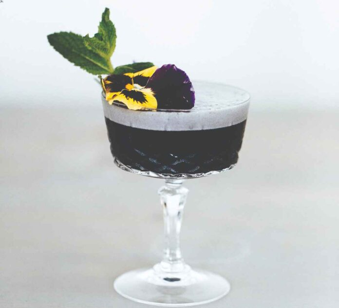 Dark purple nonalcoholic cocktail in stemmed glass with flower petal and mint garnish.
