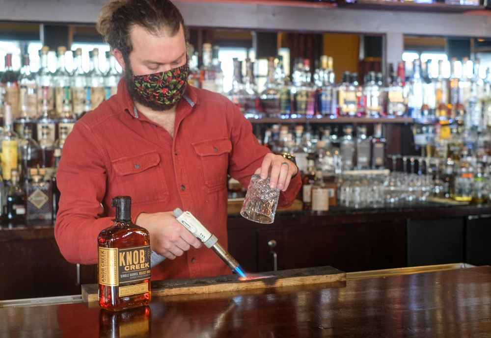 Male bartender standing behind bar and using a propane torch to char a piece of wood in preparation for infusing smoke into a cocktail glass.