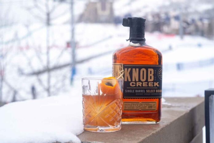 Cocktail glass filled with amber cocktail and garnished with orange peel next to Knob Creek Bourbon bottle with snowy background.
