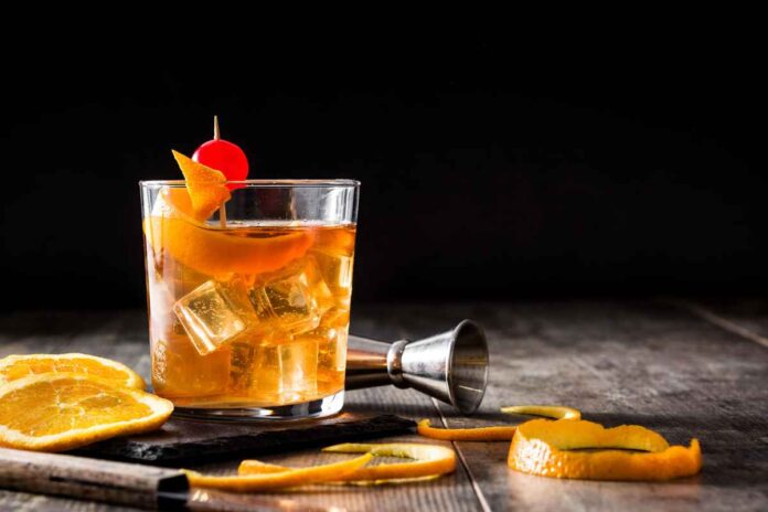 Old fashioned cocktail garnished with orange peel and cherry on wooden table with black background. Surrounded by fresh orange slices and a muddler.