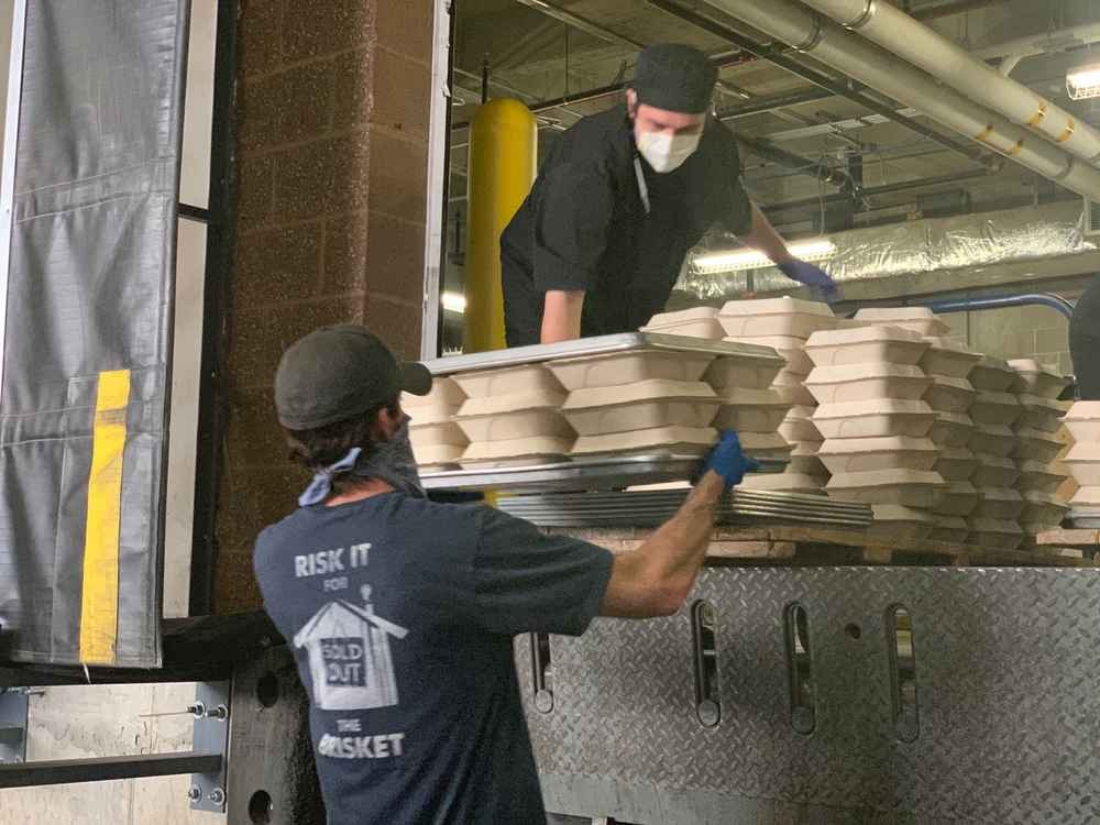 Two men unloading pallets of to-go food containers off of a truck.