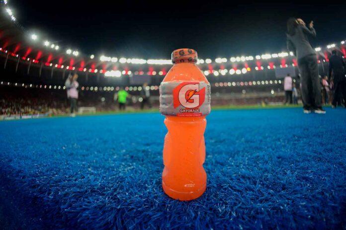 Bottle of orange Gatorade on blue turf with blurred stadium background