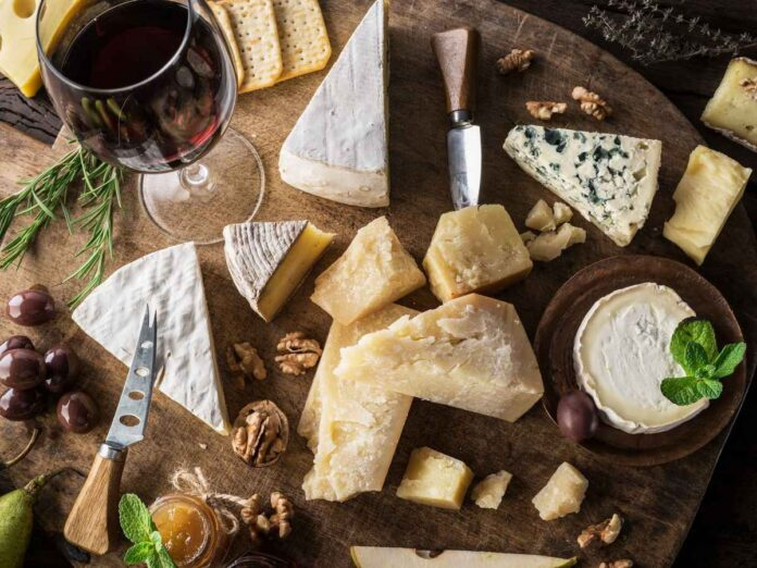 Top view of cheese platter with variety of soft and hard cheese on wooden board, plus glass of red wine.