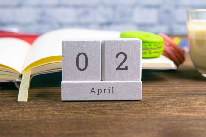 Calendar showing April 2 with an book , cup of coffee, and macaron in the background.