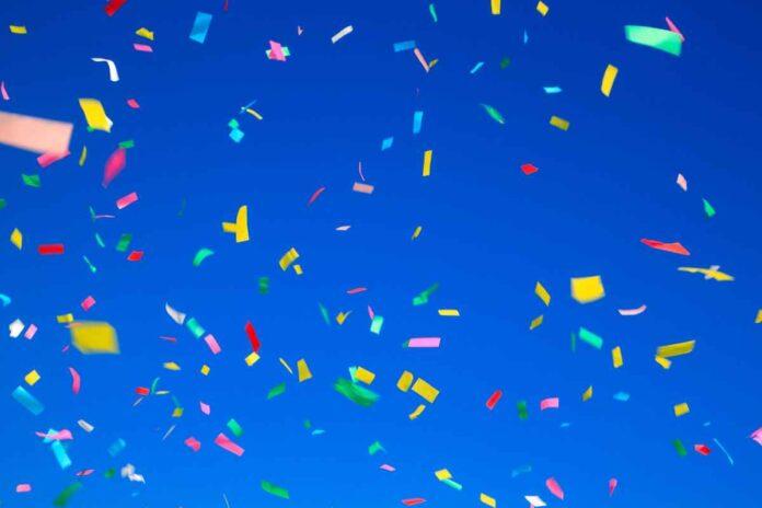 Multicolored confetti against a bright blue sky.