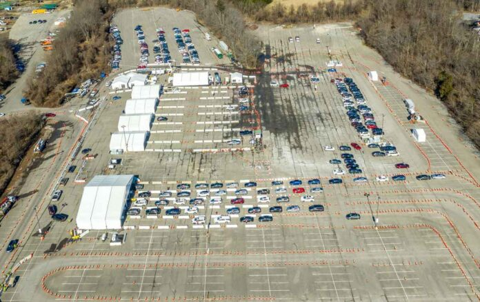 Aerial view of vaccination drive through providing mass immunization, cones separating car lanes, tents used for registration vaccination and separate waiting area.