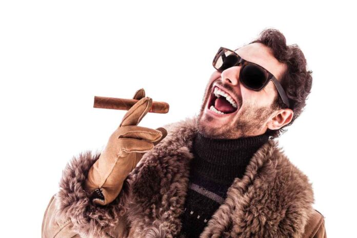 Young and rich man wearing a sheepskin coat and sunglasses, holding a cigar and laughing evilly.