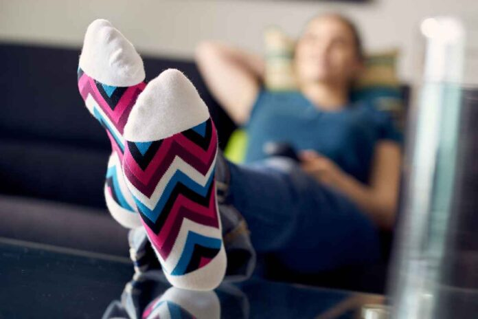 Woman relaxing on couch with feet up on table. Focus is on pink, blue and white multicolored socks.