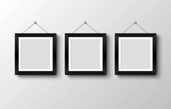 Three empty photo frames hung on a white wall.