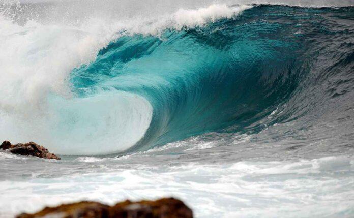 Huge turquoise blue wave crashing against the shore.