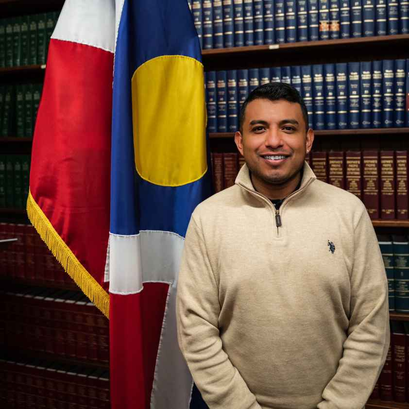 Mexican man wearing tan sweater and standing in front of Denver, Colorado flag.