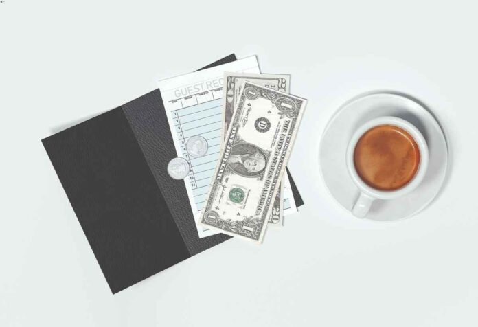 Overhead view of restaurant check folio, check, and dollar bills next to coffee cup.