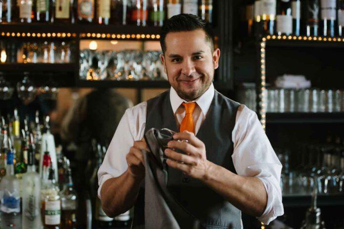 Smiling male bartender with dark hair and short beard polishing a glass behind a bar.