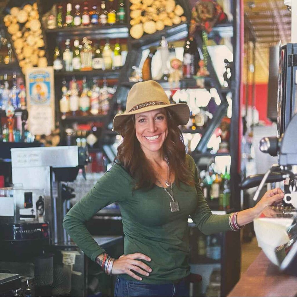White woman with long brown hair and tan brimmed hat standing behind a bar.