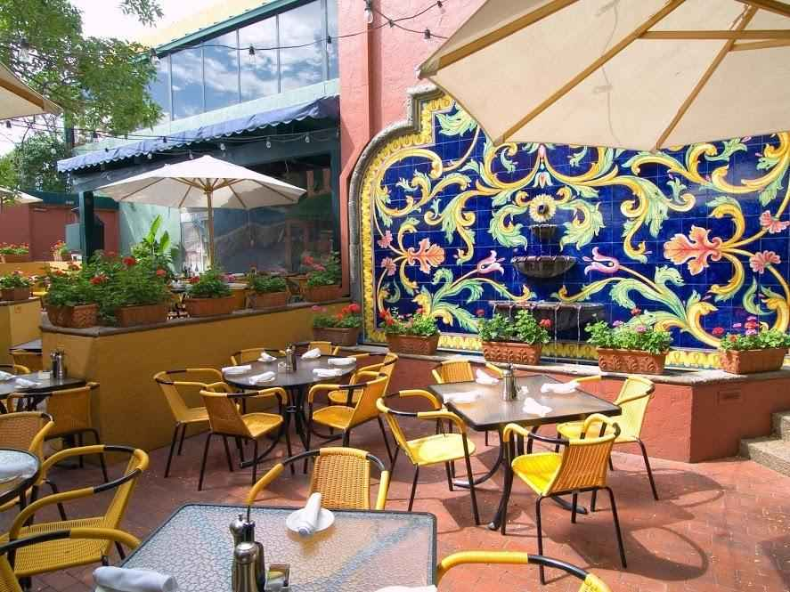 Restaurant patio with blue and yellow Mediterranean tile mosaic on wall.