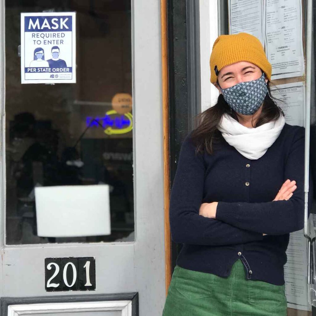 White woman wearing face mask, knit hat, and sweater leaning against door frame.
