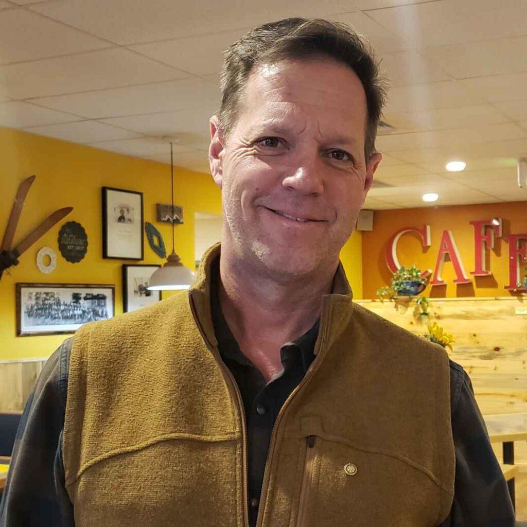 White man wearing mustard colored fleece vest.