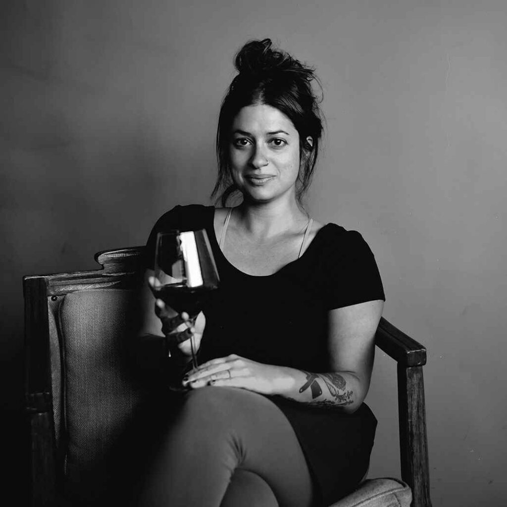 Black and white photo of light skinned woman with dark hair sitting in a chair holding a glass of red wine.