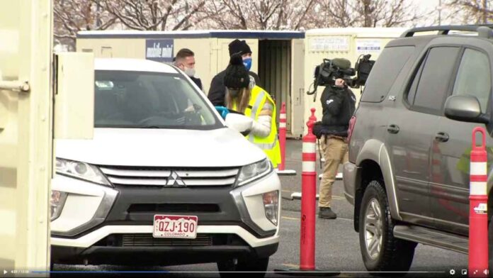White SUV being checked int by a woman wearing a mask at a drive-through COVID vaccination clinic.