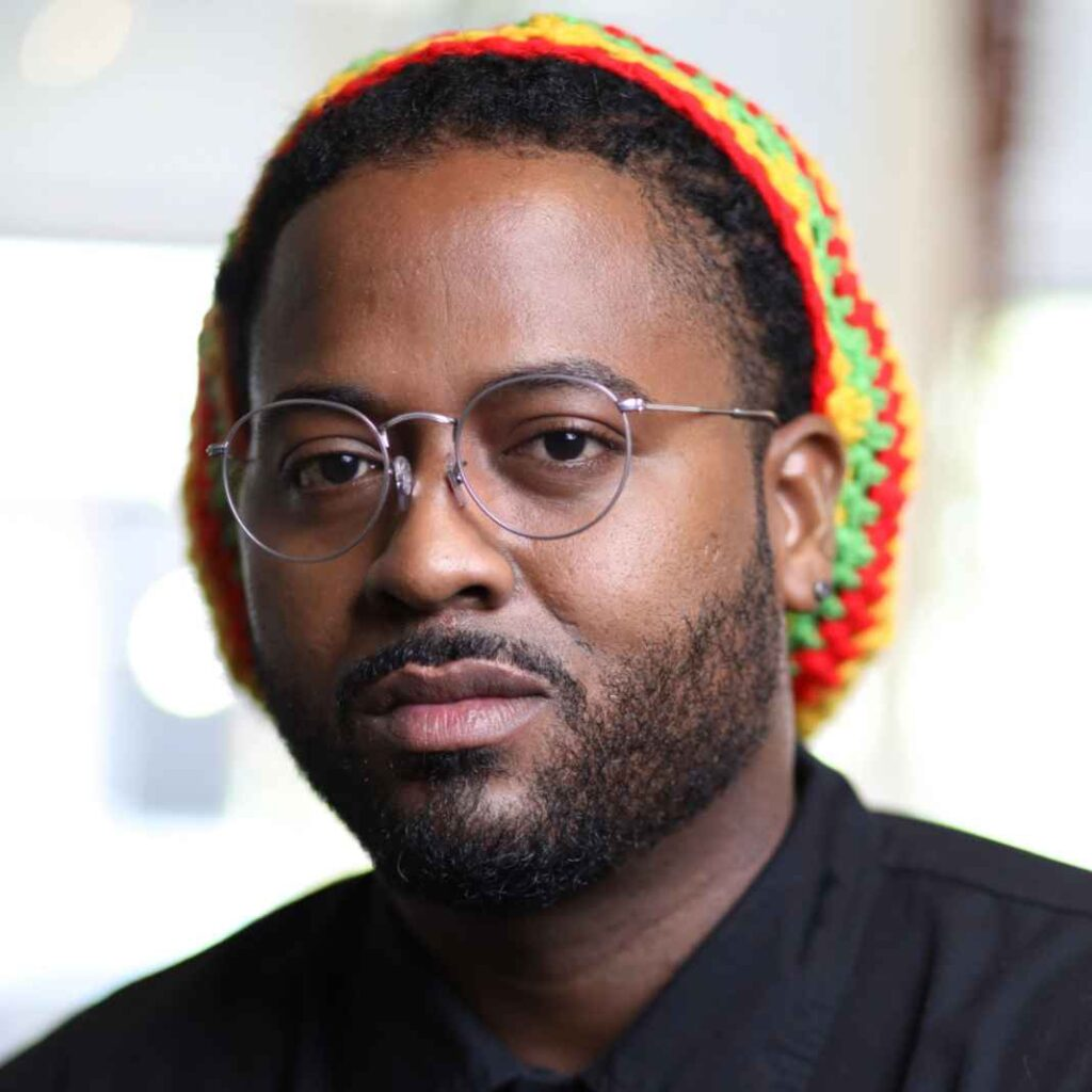 Black man wearing glasses, black shirt, and multicolored crocheted hat.