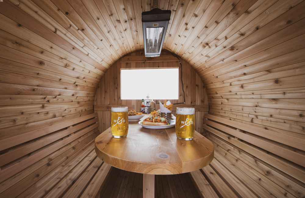 Interior of barrel sauna with wooden table, benches, food and pints of beer.