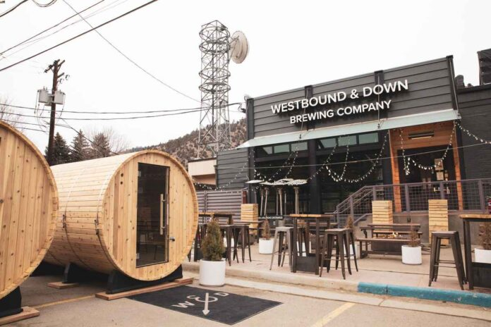 Exterior of Westbound & Down Brewing Co. with two giant barrels with glass doors for seating in the parking lot.