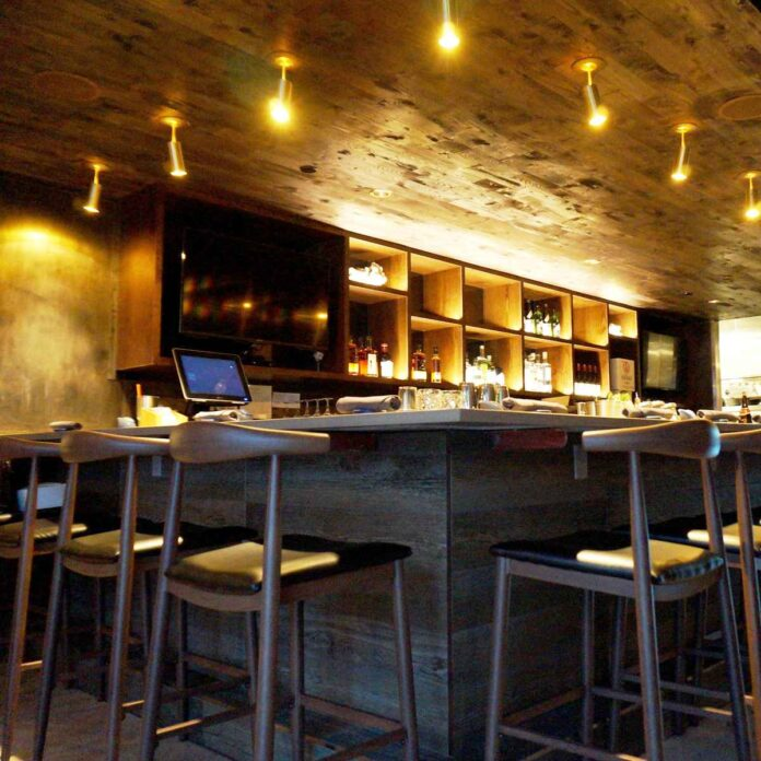 Low-angle view of bar and barstools with large screen TVs flanking liquor bottles