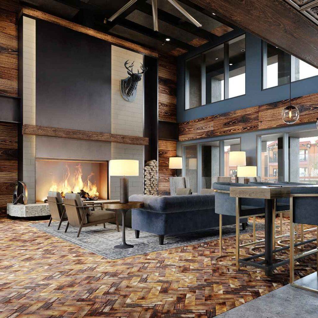 Lobby with high ceilings, brown wooden parquet floors, fireplace, couch and armchair seating.