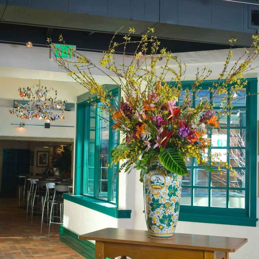 Restaurant interior painted white and teal with huge flower arrangement on a table.