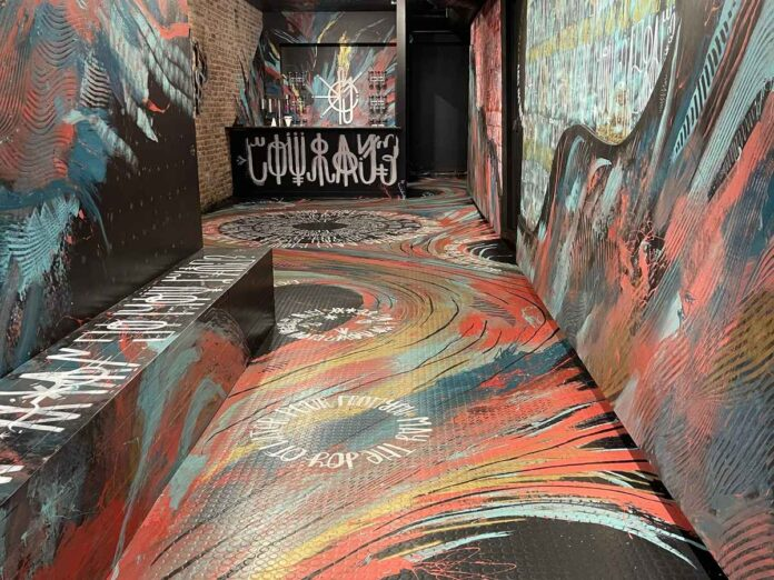 Narrow space with abstract swirls of red, blue and black on floors, walls and ceiling.